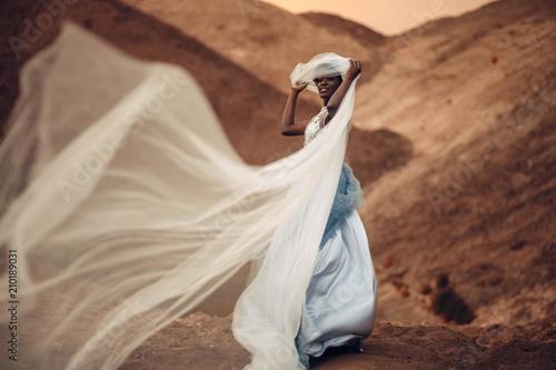 Fotografija Black bride stands and holds waving bridal veil in her hands on background of beautiful landscape