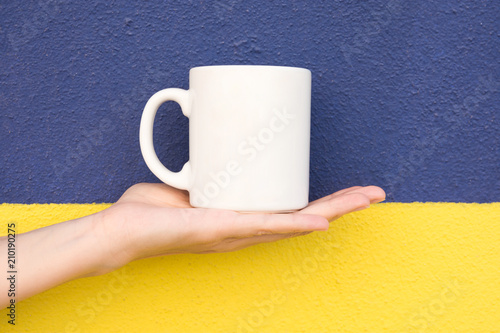 Young Caucasian Woman Holds on Hand Palm Blank Mockup White Mug on Duotone Dark Blue Yellow Painted Wall. Swedish Flag Colors. Template for Text Artwork Lettering. Trendy Minimalist Urban Style.
