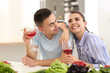 Young couple drinking wine while cooking together in kitchen