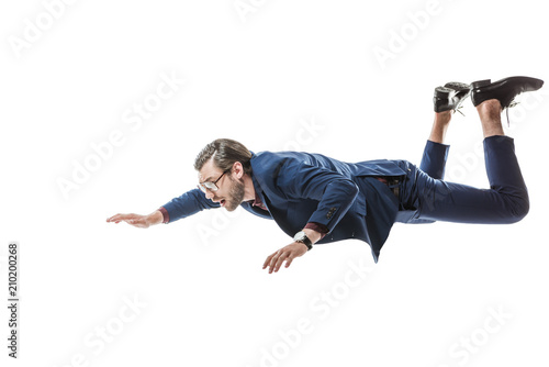 businessman in suit and eyeglasses flying and looking away isolated on white