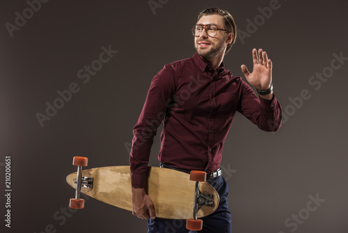 Fotografie, Obraz  handsome smiling man in eyeglasses holding longboard and looking away isolated o