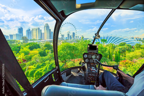 Tuinposter Singapore Helicopter cockpit interior flying on Aerial view of Singapore cityscape and garden park by the bay. Famous marina bay promenade of Singapore.
