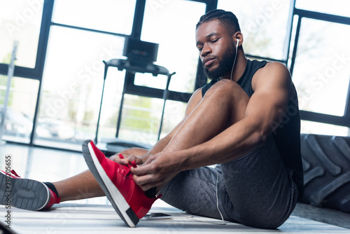 Pinturas sobre lienzo  low angle view of young african american sportsman tying shoelaces in gym