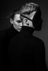 Portret kobieta z mężczyzna w twarzy masce pozuje na ciemnym tle