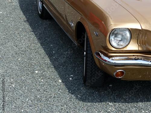 фотография  Goldglänzender amerikanischer Sportwagen der Sechzigerjahre auf grauem Schotter