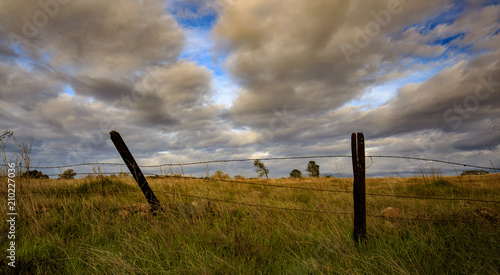 Spoed Foto op Canvas Grijze traf. Fence post with field and cloudy sky