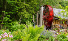 Bright Red Historic Water Wheel Turning Slowly In Garden