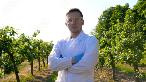 Fotografía  A young handsome (male) biologist or agronomist, wearing a white coat, wearing goggles, wearing blue rubber gloves, walks across the apple tree, the background of nature and greenery