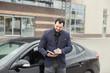 bearded businessman near a car with a phone