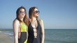beach holiday, girlfriends in swimsuit and sunglasses look into distance and laugh at quay