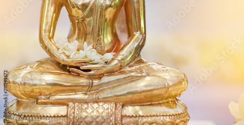 Closeup golden Buddha statue with Jasmine flower on hands.