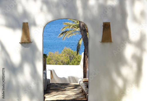 View of the Mediterranean sea through the archway of a white wall Fototapeta