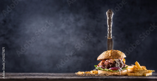 Close-up home made beef burger with knife and fries on wooden table