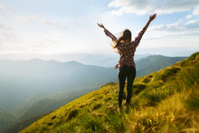Hiker Woman Standing With Hands Up Achieving The Top. Girl Welcomes A Sun. Conceptual Design. Successful Woman Hiker Open Arms On Sunrise Mountain Top. Happy Young Blonde Woman Portrait