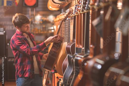 Fond de hotte en verre imprimé Magasin de musique A young man choosing a guitar