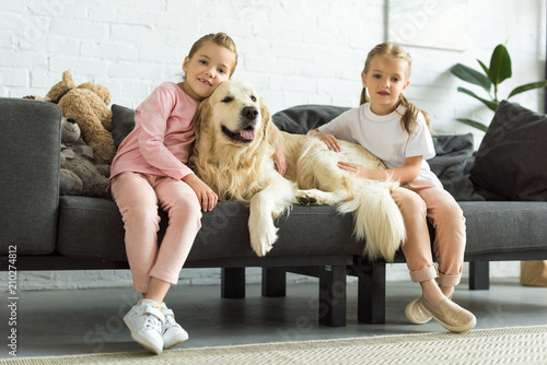 Adorable Kids Hugging Golden Retriever Dog While Sitting On Sofa At