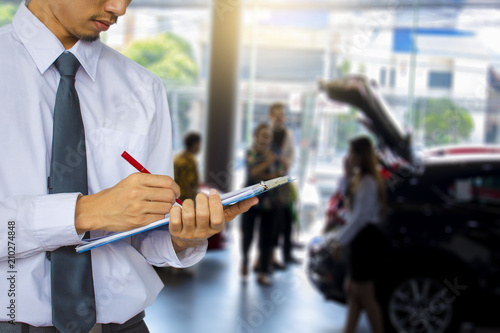 Valokuva Business man on car showroom and people blurry background
