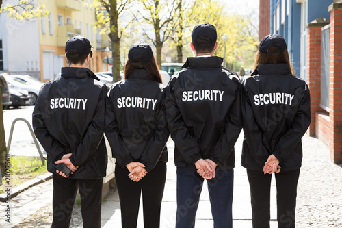 Photo Rear View Of Security Guards Standing In A Row
