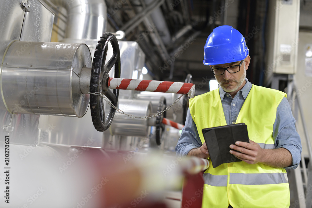 Fototapeta Industrial technician connected with tablet in recyling plant
