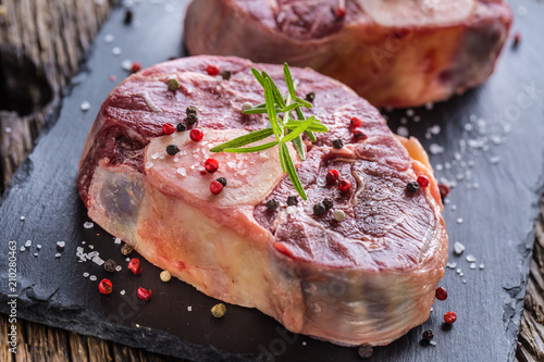 Two pieces raw beef shank on slate board and wooden table. Canvas Print