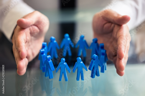 Fotografia  Businessperson Protecting Blue Human Figures Forming Circle