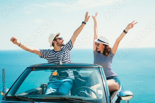 Young attractive couple posing in a convertible car, by the sea - 210323891