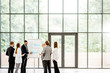 A group of business people standing together during the conference with flip chart at the modern office. Wide view with big window and copy space