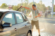Cleaning the car, car care concept - man car washing by high pressure water .