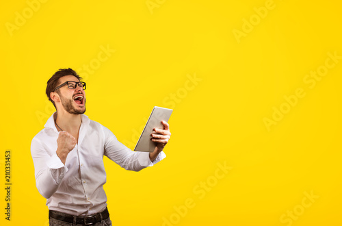 Happy man celebrating win on tablet