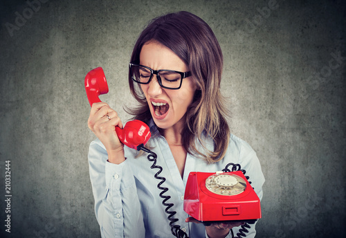angry enraged business woman yelling at the red telephone Poster