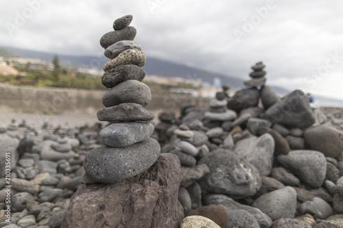 Photo sur Plexiglas Zen pierres a sable Puerto de la Cruz. Stone piles ( Cairns) on Playa Jardin, Peurto de la Cruz, Tenerife, Canary Islands, Spain. Selfmade rock-monument at the beach of Puerto de la Cruz Tenerife.