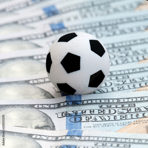 Fotografia, Obraz  Soccer ball on dollar banknotes, closeup