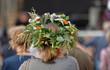 Kobieta, blond włosy, stoi tyłem (widoczna głowa i część ramion), w roślinnym, kwietnym, kolorowym wianku na głowie, w tle rozmyty tłum ludzi