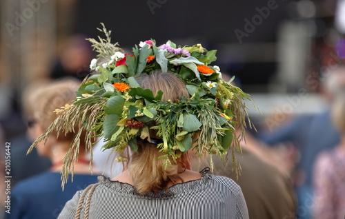 Fototapeta Kobieta, blond włosy, stoi tyłem (widoczna głowa i część ramion), w roślinnym, kwietnym, kolorowym wianku na głowie, w tle rozmyty tłum ludzi obraz