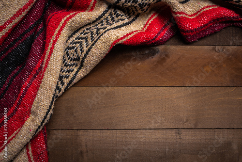 Obraz A mexican serape blanket on a wooden plank background - fototapety do salonu