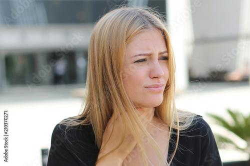 Foto  Junge Frau mit Halsschmerzen draußen im Sommer