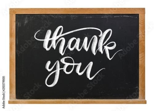 Fotografia  Thank you hand written in white chalk calligraphy lettering on a black chalkboar