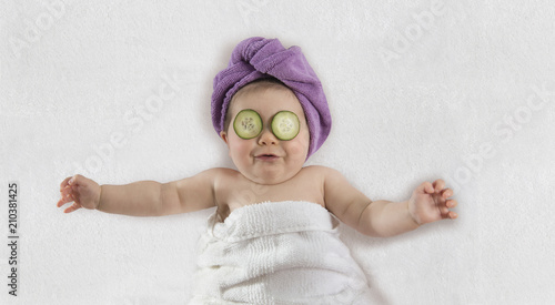 Funny baby girl wrapped in white towel with cucumbers on her eyes