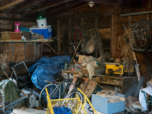 Photo Dirty old wooden garage or shed filled with a chaotic mess of all kinds of stuff