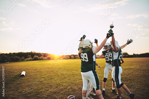 Fotografie, Tablou  Excited football players standing outside celebrating with a cha