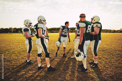 Fotografía  American football players discussing strategy together before a