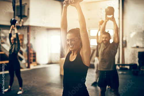 Fotografie, Obraz  Smiling young woman swinging a dumbbell at the gym