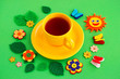 Leinwandbild Motiv Tea on a spring and summer background. A cup of tea on a green background surrounded by flowers and butterflies of felt.