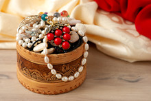 Lots Of Jewelry In A Wooden Box. Bijouterie In A Box Against The Background Of Silk Fabric. Accessories For Women's Fashion.