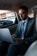 businessman in eyeglasses using laptop on backseat in car