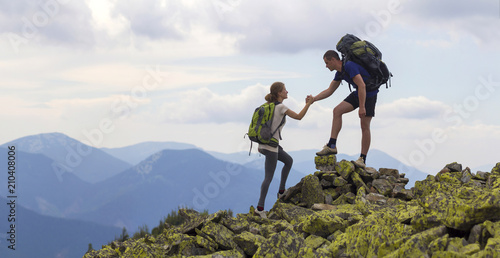 Photo sur Aluminium Alpinisme Young tourists with backpacks, athletic boy helps slim girl to clime rocky mountain top against bright summer sky and mountain range background. Tourism, traveling and healthy lifestyle concept.