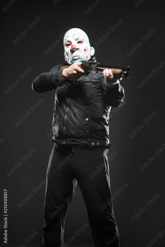Fototapeta robber in the mask clown stands with a gun in his hands
