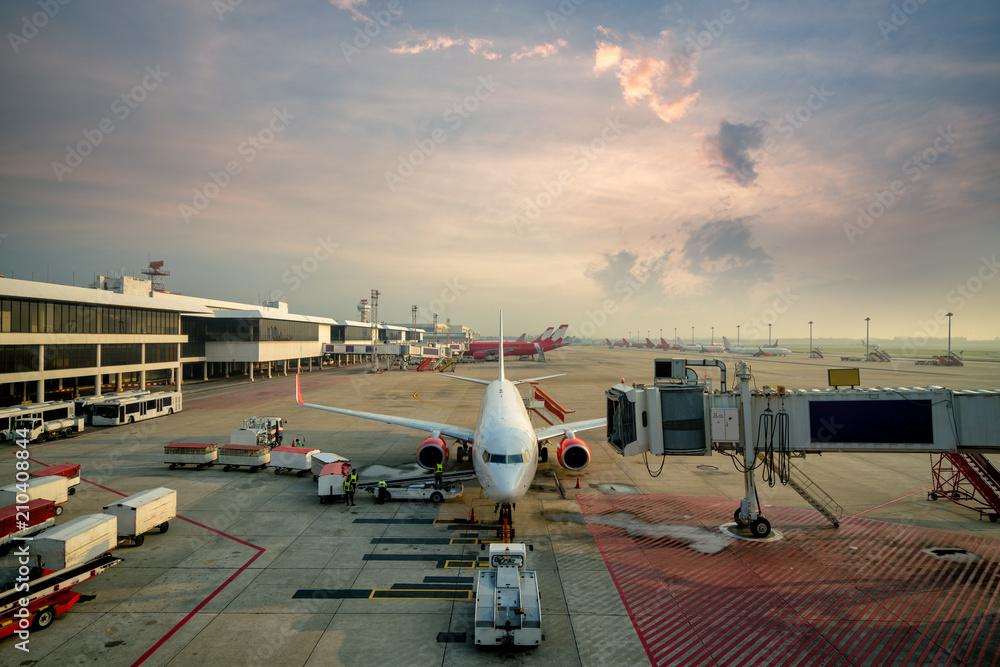 Fototapeta Modern passenger airplane parked to terminal building gate at international airport.