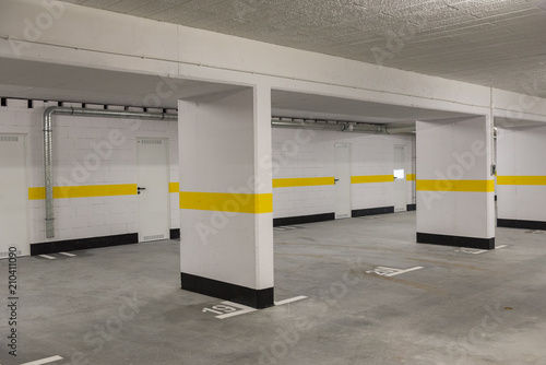 Fotografia, Obraz Typical underground car parking garage in a modern apartment house