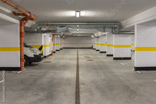 Fototapeta Typical underground car parking garage in a modern apartment house. obraz